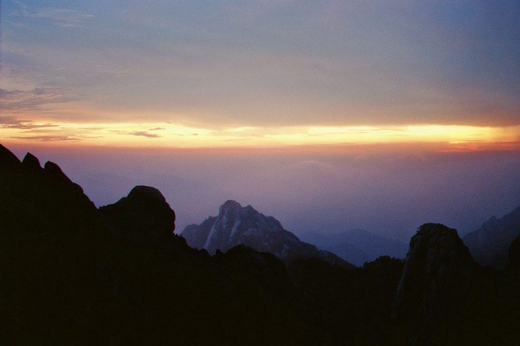 Sonnenuntergang auf chinesischen Bergen mit einem Streifen Gold am Horizont.